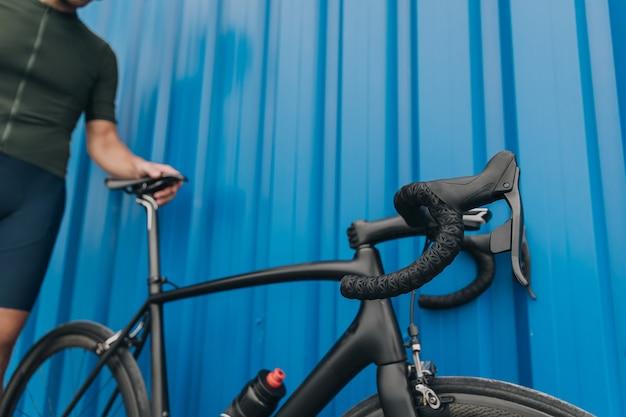Close-up de atleta masculino posando ao ar livre com bicicleta preta