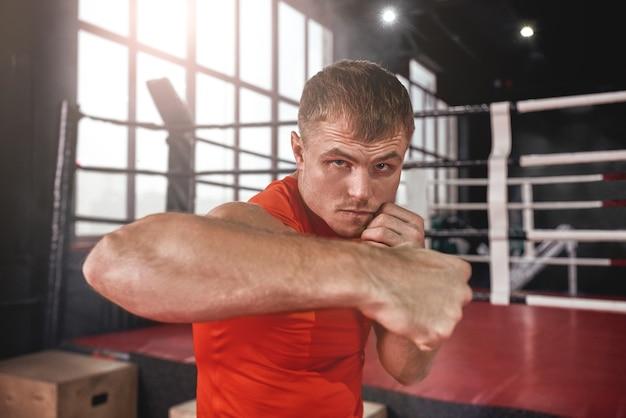 Close-up de atleta musculoso focado em roupas esportivas, realizando soco lateral. jovem boxeando com sombra em frente ao ringue de boxe colorido