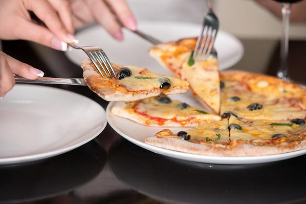 Close-up de azeitonas e queijo pizza italiana com garfo e faca