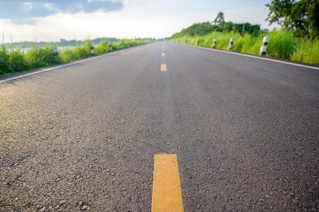 Close-up de baixo ângulo da estrada pavimentada preta em uma área rural aberta com ênfase na linha amarela no centro. estradas pavimentadas de preto com belos prados ao longo do caminho.