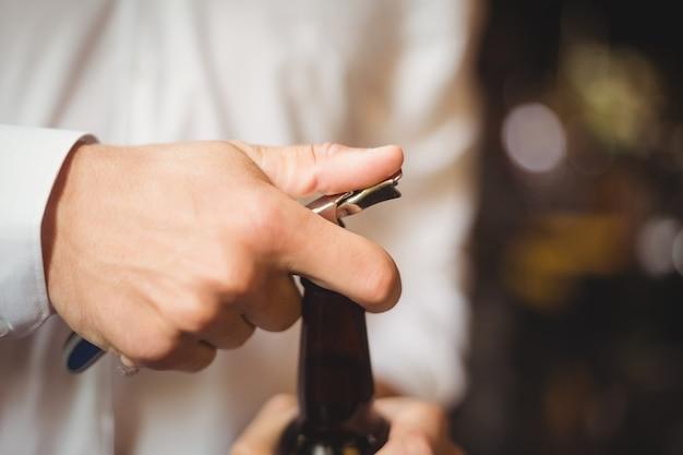 Close-up de barman, abrindo uma garrafa de cerveja