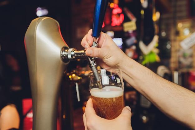 Close-up de barman mão na torneira de cerveja, derramando uma cerveja de pressão.