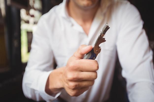 Close-up de barman um abridor de garrafas