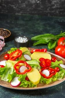 Close up de batatas frescas descascadas cortadas com pimenta vermelha, rabanetes, tomates verdes em um prato marrom e mede as especiarias em uma superfície de cores pretas e verdes