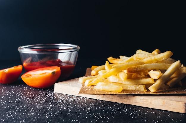 Close-up de batatas fritas com ketchup em fundo preto