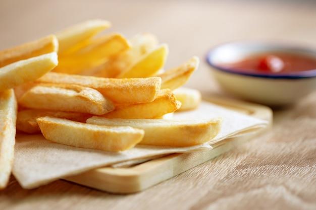 Close-up de batatas fritas com molho de tomate em cima da mesa, junk food insalubre