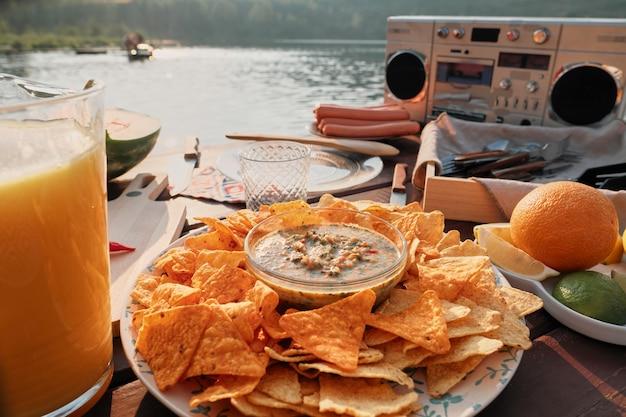 Close-up de batatas fritas com molho na mesa com outros petiscos preparados para a festa ao ar livre