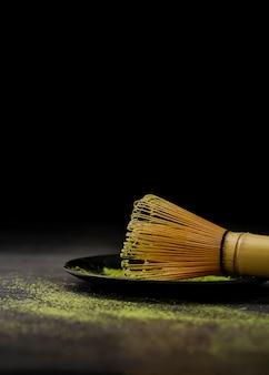 Close-up de batedor de bambu com pó de chá matcha