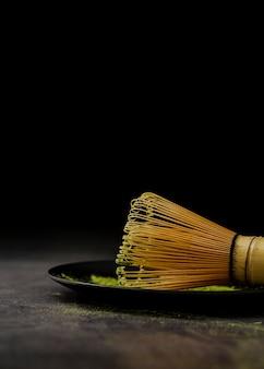 Close-up de batedor de bambu no prato com fósforo chá em pó
