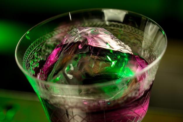 Close up de bebida alcoólica de coquetel em luz de néon multicolorida