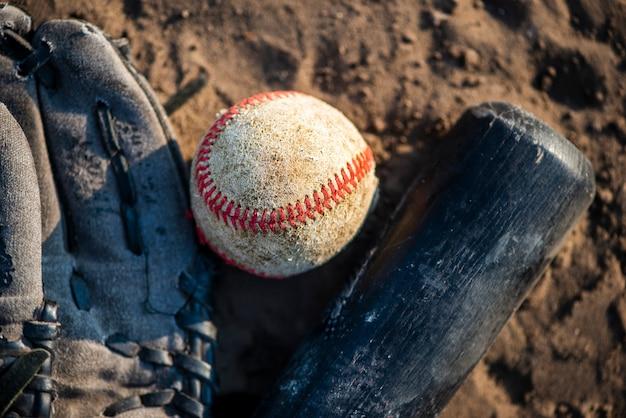 Close-up de beisebol e taco na sujeira