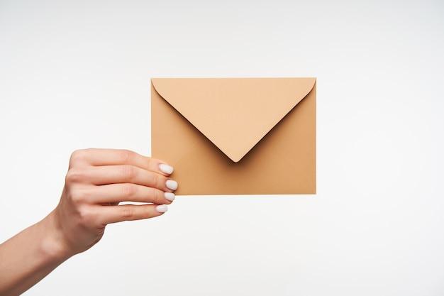 Close-up de belas mãos segurando um envelope de papel em branco
