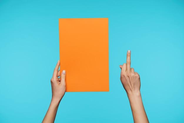 Close-up de belas mãos segurando uma folha de papel em branco