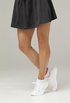 Close-up de belas pernas femininas no desgaste do esporte sobre fundo cinza