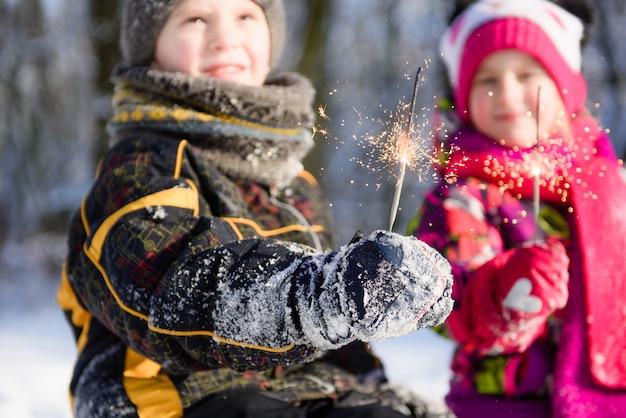 Close-up de bengalas nas mãos das crianças no inverno