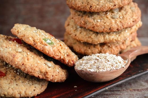 Close-up de biscoitos de aveia caseiro em um prato e uma colher com flocos de aveia