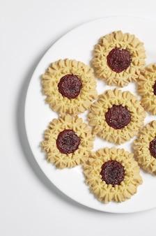 Close-up de biscoitos doces com recheio de prato no fundo branco, vista superior