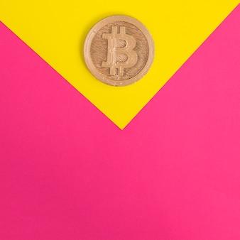 Close-up de bitcoin em fundo amarelo e rosa