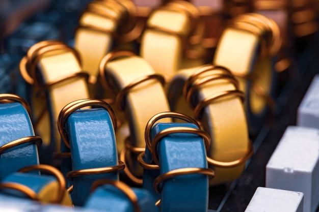 Close-up de bobinas amarelas e azuis envoltas em núcleos de pó de ferro na fábrica para produção de equipamentos industriais e domésticos, geladeiras e freezers. produção de conceito de transmissor