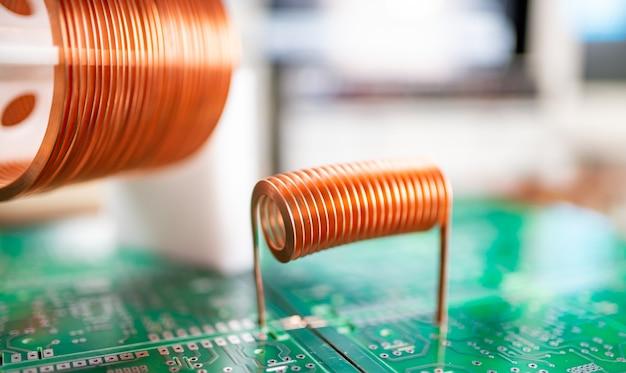 Close-up de bobinas grandes e pequenas com fio de cobre em um microcircuito verde
