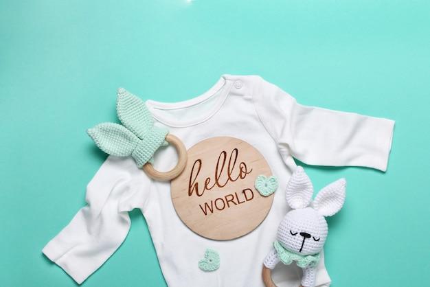 Close up de bodysuiteco de brinquedo de madeira branco de bebê, pufe e mordedores de madeira tablet hello world