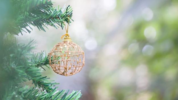 Close-up de bola de ouro para o natal em luzes desfocadas
