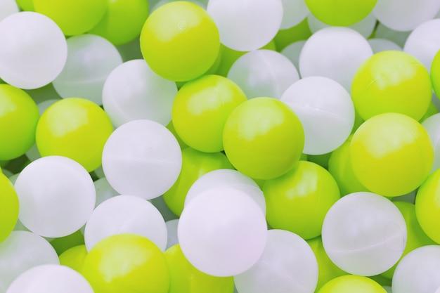 Close-up de bolas brancas e amarelas de plástico na piscina seca no parque infantil
