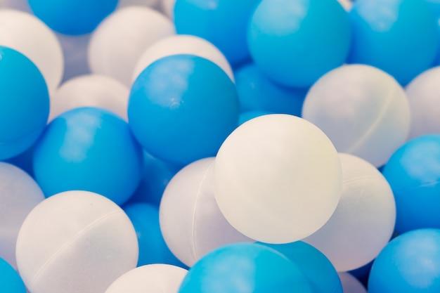 Close-up de bolas brancas e azuis de plástico na piscina seca no parque infantil