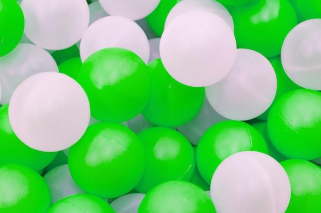 Close-up de bolas brancas e verdes de plástico na piscina seca no parque infantil