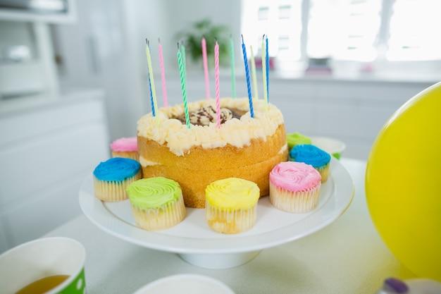 Close up de bolo de aniversário em carrinho com cupcake e velas