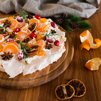 Close-up de bolo de merengue, decorado com fatias de laranja e rosa mosqueta