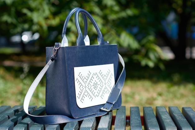 Close-up de bolsa feminina muito na moda, confeccionada em duas cores: azul e branco. ele fica no banco do parque. inclui cinto longo e bolso em relevo. a foto foi feita em um fundo branco.