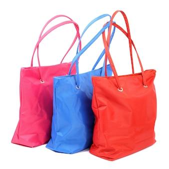 Close up de bolsas rosa azul e vermelho