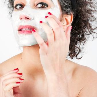 Close-up, de, bonito, mulher jovem, aplicando, branca, máscara rosto