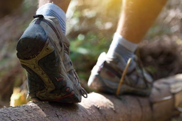 Close-up de botas de caminhada. menino turista pisa em um tronco