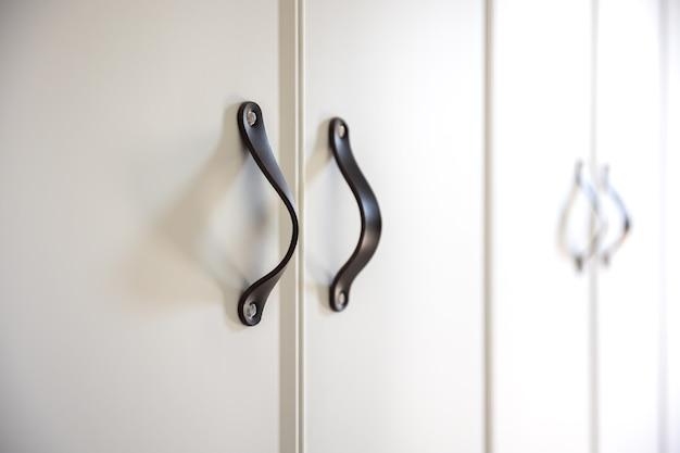 Close-up de botões pretos em um armário branco.