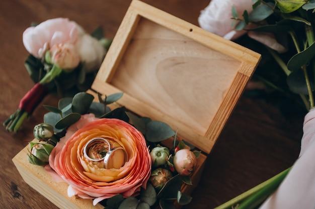 Close up de bouquet de noiva pastel com alianças de casamento