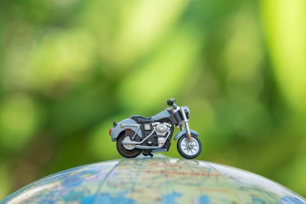 Close-up de brinquedo de motocicleta em miniatura no mapa de balão do mundo