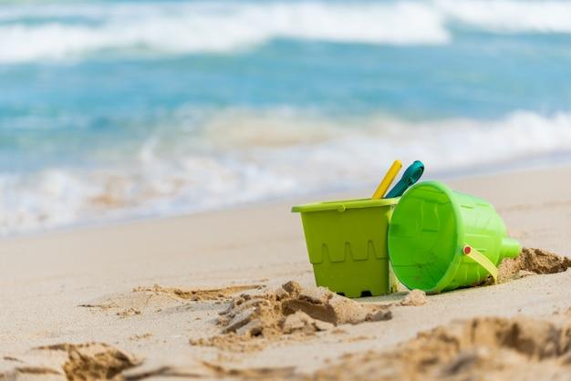 Close up de brinquedos de areia de duas crianças verdes com baldes e pás em uma praia no havaí
