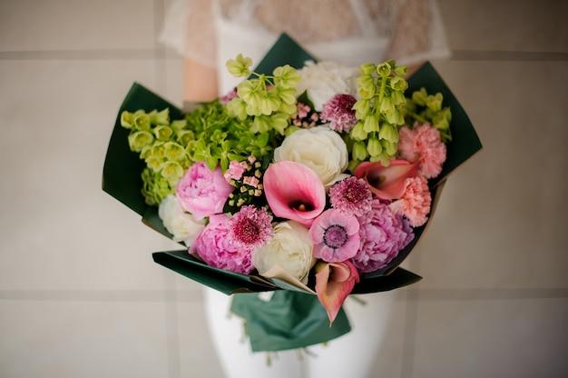 Close-up de buquê com várias flores no embrulho verde