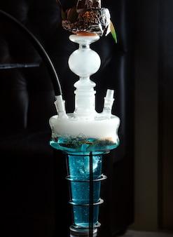 Close-up de cachimbo de água com frutas na água azul