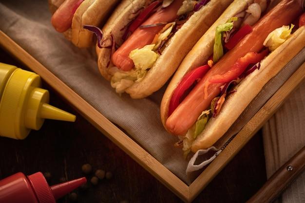 Close-up de cachorros-quentes com mostarda e ketchup, em madeira rústica e estilo escuro