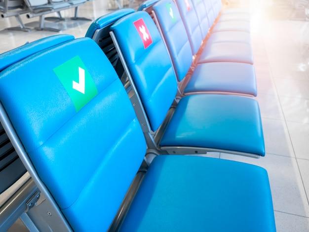 Close-up de cadeiras de espera vazias com sinal de distanciamento social