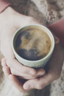 Close up de café expresso saboroso com espuma amarela saborosa em copo de cerâmica verde. mãos masculinas segurando cálidas bebidas quentes.
