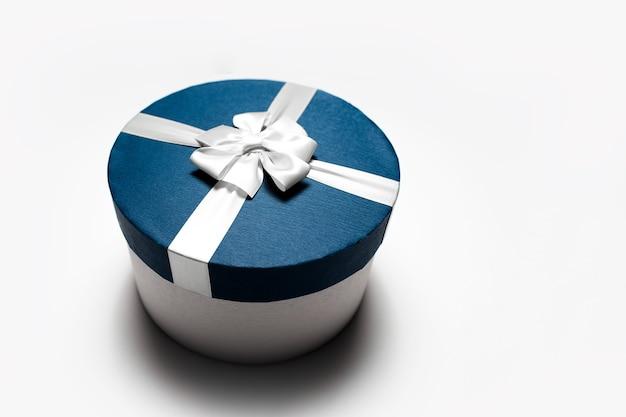 Close-up de caixa de presente redonda azul com laço isolado