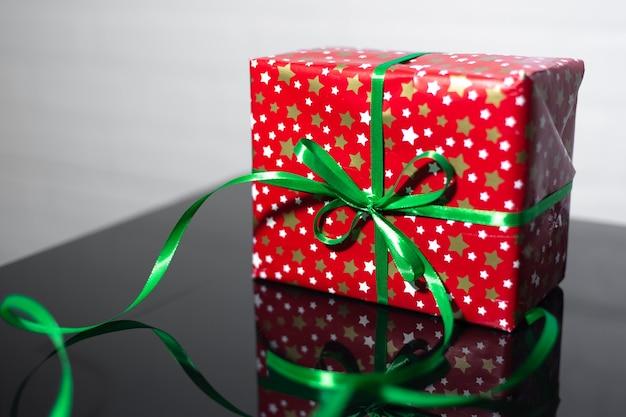 Close-up de caixa de presente vermelha com laço verde em vidro preto