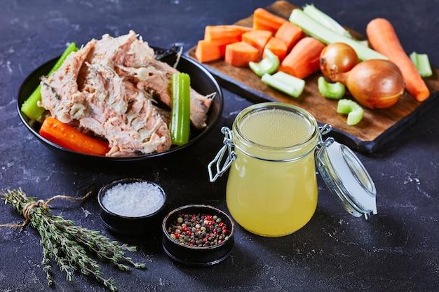 Close-up de caldo de peixe cozido lentamente ou caldo de salmão em uma jarra de vidro sobre uma mesa de concreto com carne de peixe, ossos e vegetais em uma tigela
