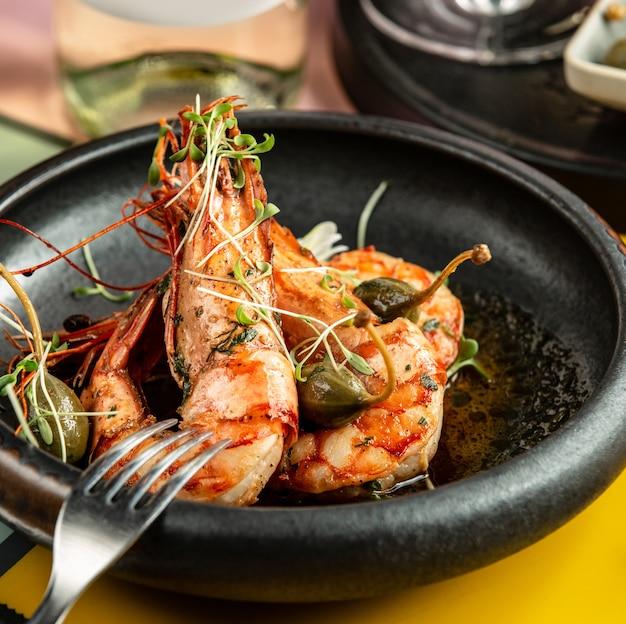 Close-up de camarão frito, guarnecido com picles e ervas frescas