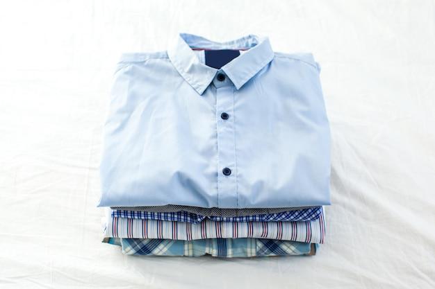 Close up de camisas passadas e dobradas na mesa em casa