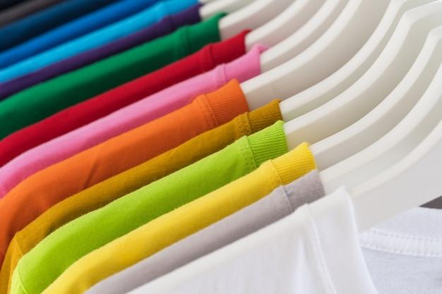 Close up de camisetas, roupas em cabides em branco